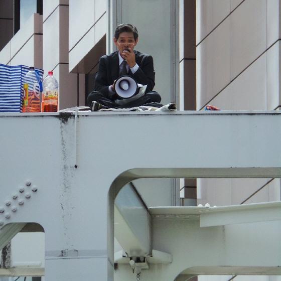 平成26年(2014年)6月29日午後2時10分頃、東京都新宿区西新宿の歩道橋の鉄枠の上で、腐れパヨク男が「集団的自衛権の行使容認に反対」演説後、ペットボトルに入ったガソリンのようなものを頭からかぶり、ラ