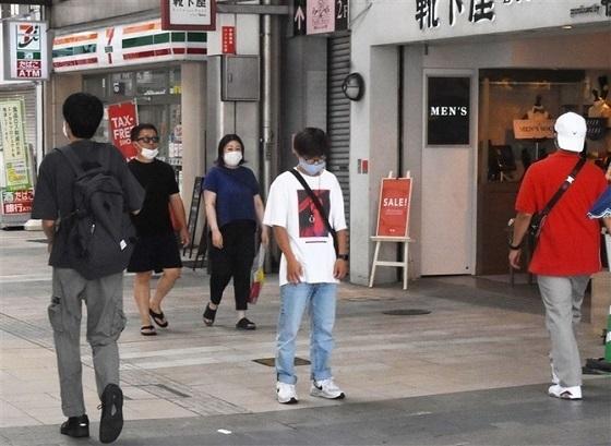 終戦記念日のサイレンに合わせて黙とうする男性(中央)。足を止める人はまばらだった=15日正午、熊本市
