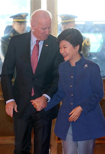 2013年12月6日、青瓦台で出迎えた朴槿恵大統領の手を握り締めるバイデン副大統領(新潮社)