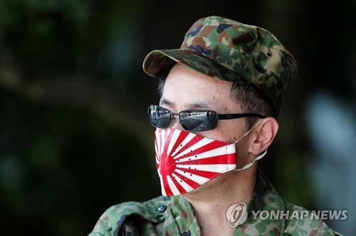 日本の太平洋戦争敗戦75周年である15日、靖国神社で軍服姿で旭日旗の文様を入れたマスクをつけた男性が、参拝の順番を待っている。