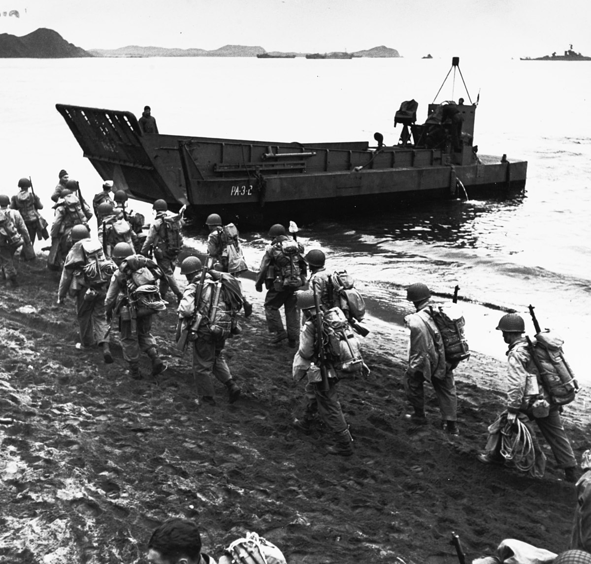 1200px-Troops_marching_up_beach_during_loading_for_Kiska_operation,_13_August_1943_(80-G-475421)
